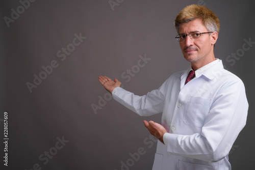 Deurstickers Ontspanning Man doctor with blond hair against gray background