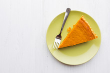 Slice Of Pumpkin Pie Photographed From Above Over White Wooden Background
