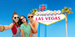 travel, tourism and vacation concept - group of happy female smiling friends in sunglasses taking selfie over welcome to fabulous las vegas sign background