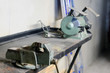 Metal workshop. Vise and bench grinder on metallic workbench. Copy space.