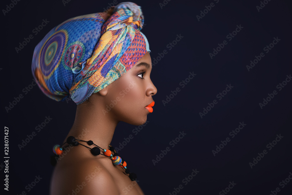 Fototapeta African woman with a colorful shawl on her head