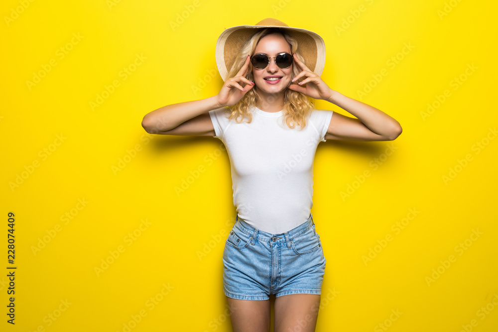 Fototapety, obrazy: Hello, summer. Attractive young woman in sunglasses is posing with straw hat isolated on yellow background.