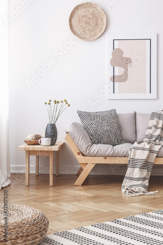 Wicker decorations and a painting on a white wall above a wooden sofa with cushi Wallpaper Mural