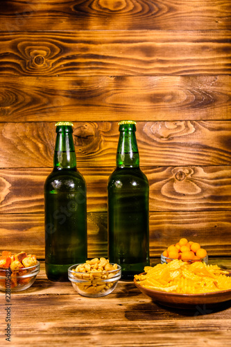Tuinposter Bier / Cider Two bottles of beer and different snacks on wooden table