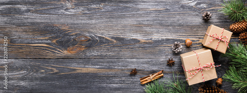 Fototapeta Christmas gifts in rustic stlye. Two gift boxes with cinnamon sticks, pine cones, anise stars and pine branches on wooden table. Top view, banner for website. obraz