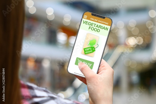Vegetarian food idea, girl with frameless phone on blurred mall background