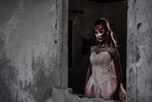 Female Zombie Corpse Standing In Front Of Grunge Wall In Abandoned House. Horror And Ghost Concept. Halloween Day Festival And Scary Movie Theme. Haunted House Theme. Dark Tone Film