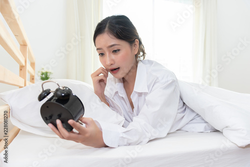 Photo Asian woman shocked when wake up late by forget to setting alarm clock at night and having meeting appointment and working in morning today