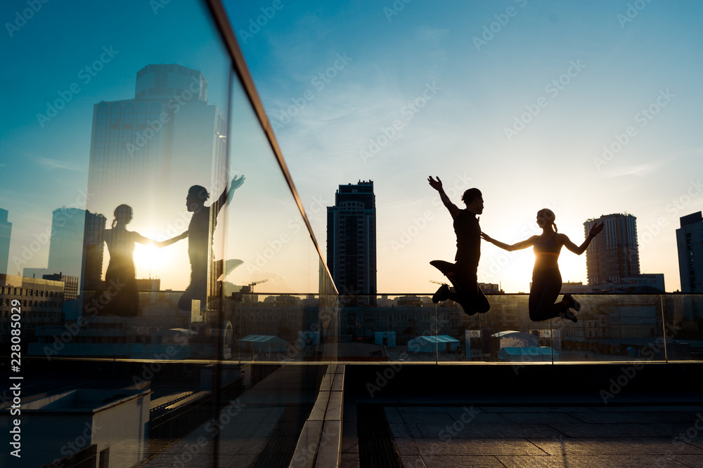 Fototapety, obrazy: Sporty couple in a jump