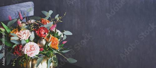Leinwand Poster Autumn floral bouquet in punpkin vase on black chair, banner