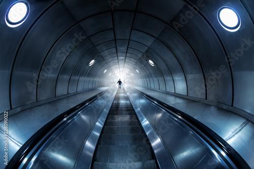 Moderne Rolltreppe durch einen stählernen, dunkelen Tunnel in das Licht Wallpaper Mural