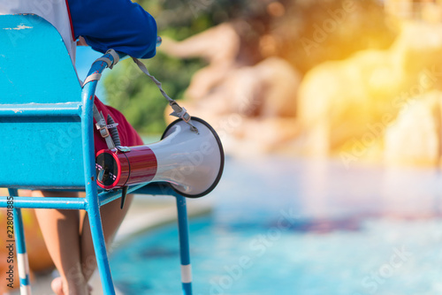 Obraz na płótnie lifeguard sitting on chair with megaphone at poolside for guarding lives