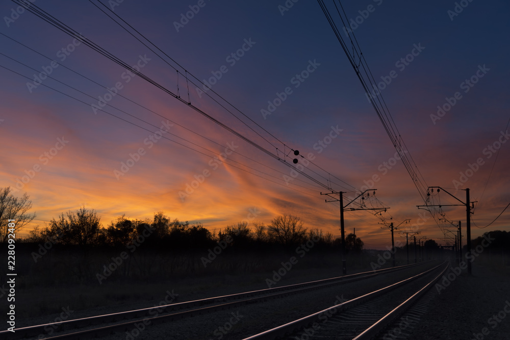 Fototapeta Dark silhouettes railway infrastructure against background of colorful dramatic sunset. View of railroad going straight away to sun and beyond the horizon. Transportation and travel concept.