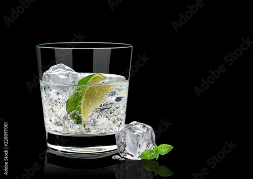 Photo Vodka lime, mojito or gin tonic  with lime wedge and ice in rocks glass on black