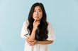 Thinking scared young asian beautiful woman posing isolated over blue background.