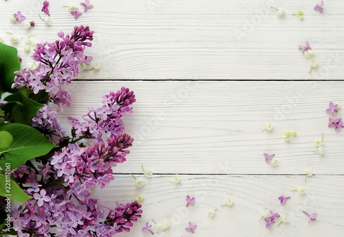 Fotobehang Bloemen Floral pattern of a branch of lilac spring flowers on a white wooden background. top view. flat lay. Holiday concept. Copy space