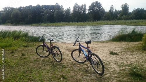 Two mountain bikes next to a lake