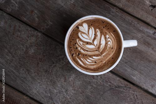 Nice shape of latte art coffee serve on wooden plate