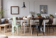 Real Photo Of An Eclectic Dining Room Interior With Various Chairs At The Table, Lamp And Painting With Ducks