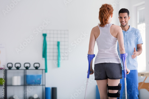 Valokuvatapetti Patient with crutches during a rehabilitation with her physiotherapist in a clin