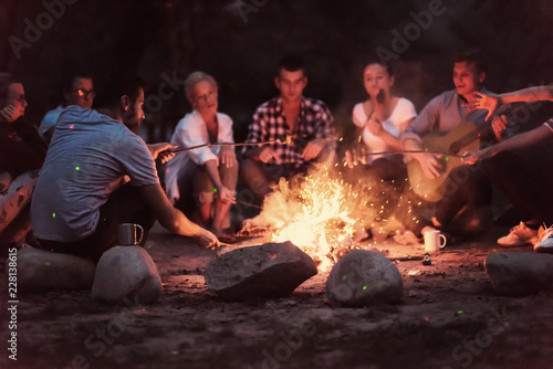 Obraz young friends relaxing around campfire - fototapety do salonu
