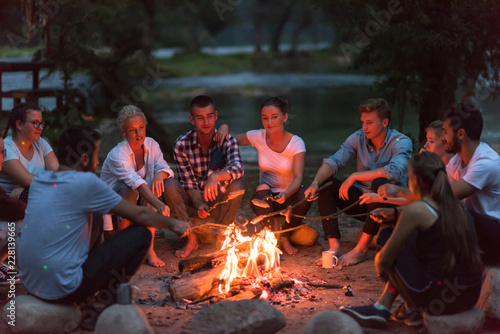 Photo young friends relaxing around campfire