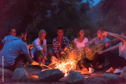 young friends relaxing around campfire - 228139800