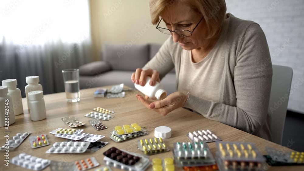 Valokuva Old female taking capsules from bottle self-medication pills addiction obsession