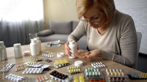 Valokuva  Senior lady taking too much pills, feeling unwell, heart problem self-medication