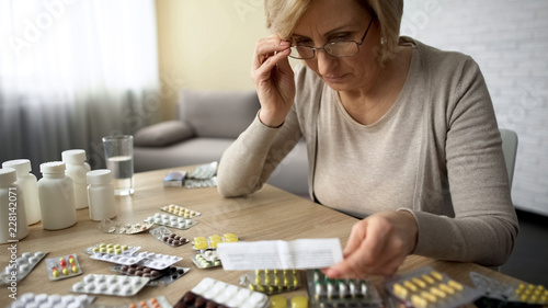 Retired female in glasses reading medicine instruction, pharmaceutical industry Canvas-taulu