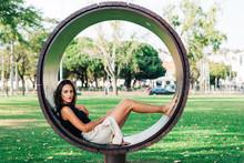 Brunette Sitting In Modern Round Bench