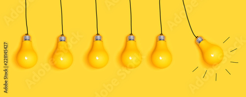 Obraz Many hanging light bulbs on a yellow background - fototapety do salonu