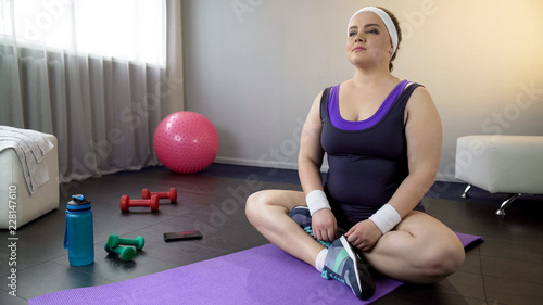 Fotografie, Obraz Plump female taking lotus position to meditate, recover breath after workout