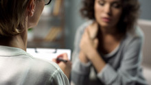 Female Psychologist Listening To Young Lady During Personal Session, Depression