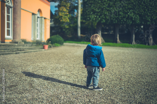 Photo Toddler standing outside in courtyard