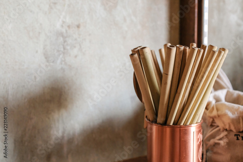 Carta da parati Close up of natural color bamboo straws in rose gold bronze cup  with loft concr