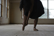 Low Section Of Woman Wearing Ballet Shoe While Standing On Wooden Floor In Old Building