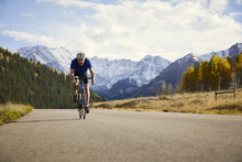 Man Riding Bicycle At Mountain Landscape, Aspen, Colorado, USA