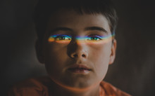 Close-up Portrait Of Cute Boy With Spectrum On Eyes In Darkroom At Home