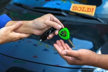 The Salesman Gave The Car Keys To Customers With Humility In Front Of Dark Blue Used Car And Blurred Yellow Label With Red Wording Sold!