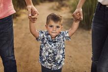 Portrait Of Cute Boy Among Parents Holding Hands
