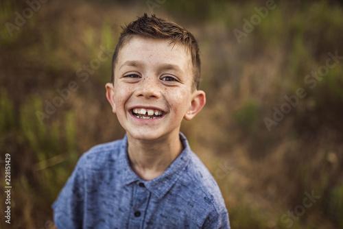 Portrait of cheerful boy standing on field