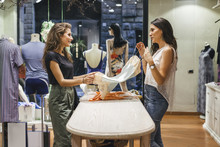Woman Showing Dresses To Customer At Store