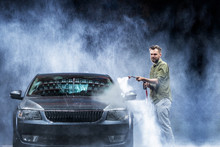 A Man With A Beard Or Car Washer Washes A Gray Car With A High-pressure Washer At Night In A Shop Wash