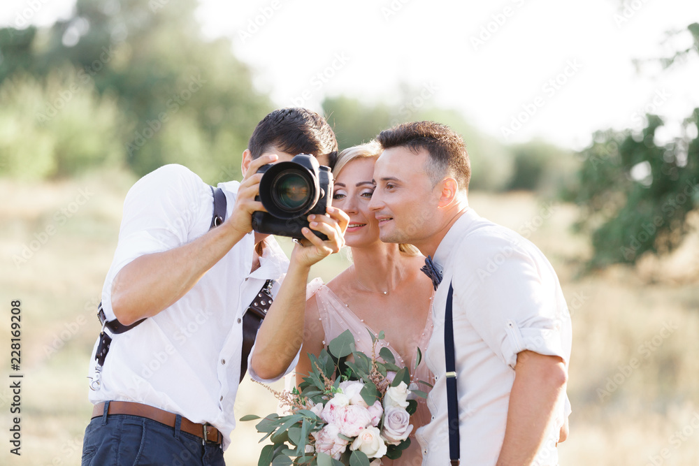 Fototapety, obrazy: wedding photographer takes pictures of bride and groom