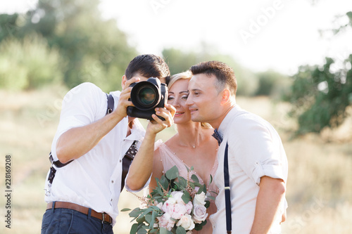 Obraz wedding photographer takes pictures of bride and groom - fototapety do salonu