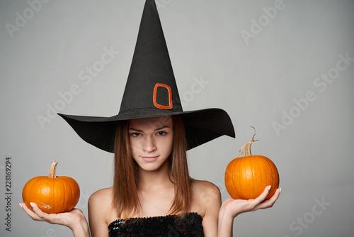 Closeup of serious Halloween witch holding orange pumpkins looking at camera int Wallpaper Mural