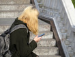 Blonde girl in black clothing sitting with a smartphone in hands on the street. Concept for social networks, online dating, reading or listening music with headphones