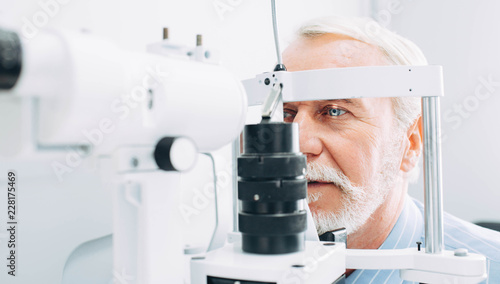 Fotografía  Senior patient checking vision with special eye equipment