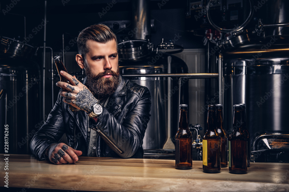 Fototapeta Stylish bearded biker dressed black leather jacket sitting at bar counter in indie brewery.